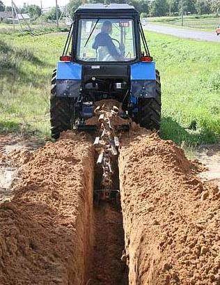 Трактор копает траншею
