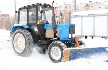 Трактор убирает снег