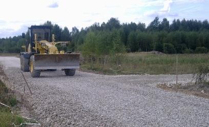 Трактор едет по гравийной дороге